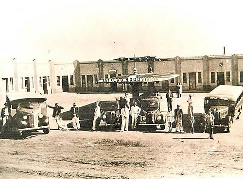 Pessoas e carros em frente à estação